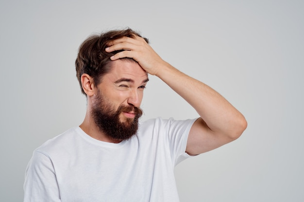 Man holding his head pain stress emotions light background