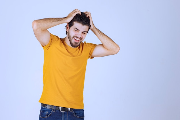 Man holding his head with both hands and looking excited.