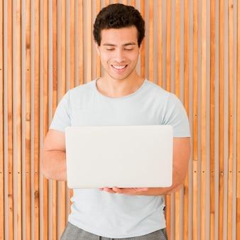 Мужчина держит свой ноутбук и работает