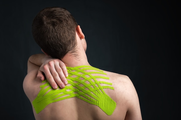 Man holding his neck with kinesiology medical tape applied to relieve back pain