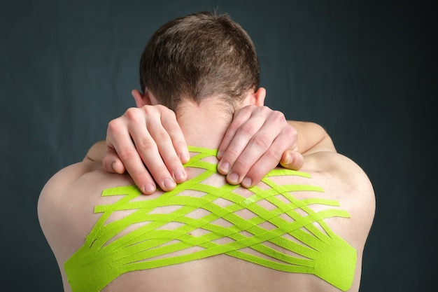 Мужчина держит шею кинезиологической медицинской лентой, применяемой для облегчения боли в спине