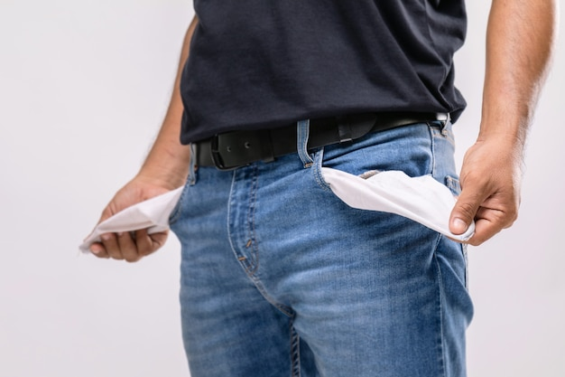 Man holding his pants pocket to show no money inside