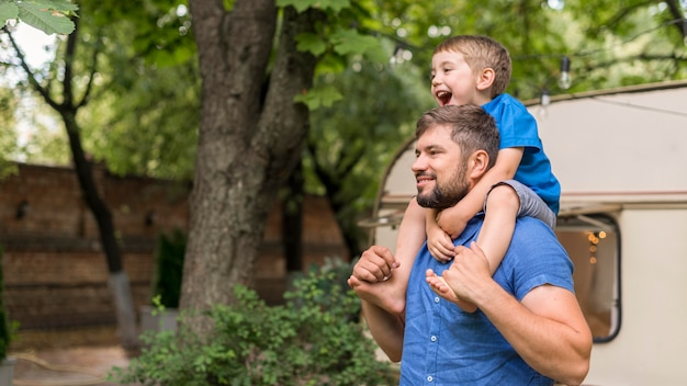 コピースペースで彼の肩に息子を抱きかかえた