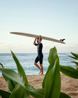 그의 서핑 보드를 들고 남자