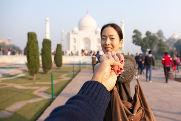 Man holding his wife hand showing wedding ring with taj mahal in background.