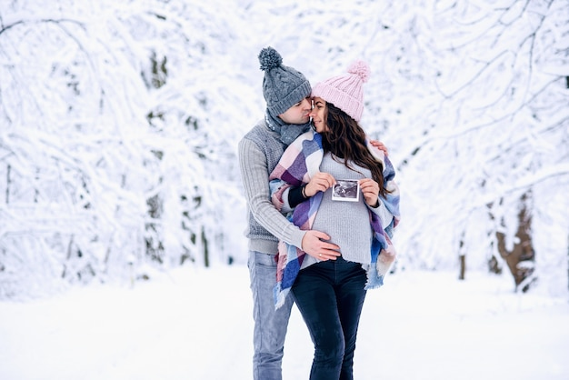 Man holding his wife's pregnant belly and kisses her gently on the nose on snowy winter park