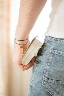 Man holding holy bible over gray background for copy concept for religion, praying, education and bible study