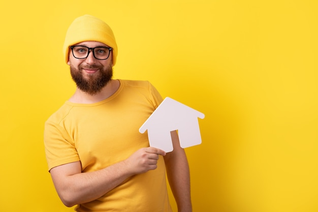 Man holding home over yellow background, mortgage loan concept