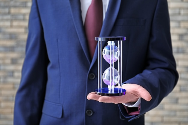 Man holding hourglass on blurred background