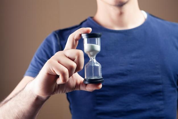 Человек, держащий песочные часы на коричневом фоне