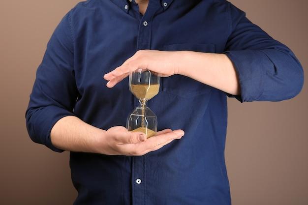 Человек, держащий песочные часы на цвете. концепция управления временем