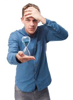 Man holding an hourglass with a hand on head