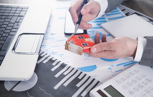 Человек, держащий модель дома и расчет ссуды финансов и инвестиций для недвижимости.