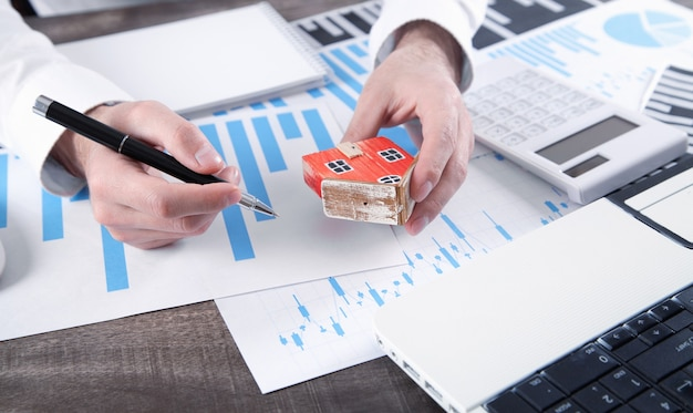 Man holding house model and calculating loan of finance and investment for real estate.