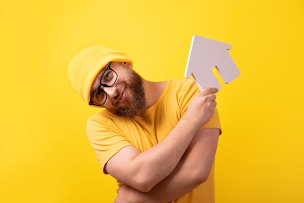 Man holding house representing home ownership and the real estate business, guy over yellow background