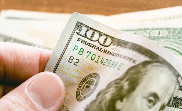 A man holding a hundred dollar bill in close up photo