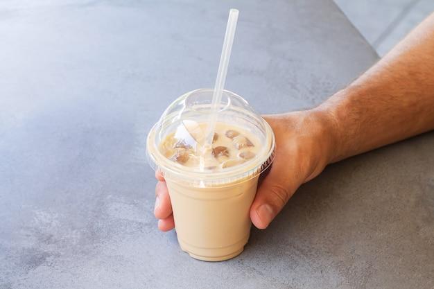 거리 카페에서 테이크아웃 플라스틱 컵에 아이스 커피나 라떼를 들고 있는 남자
