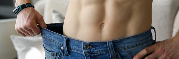 Мужчина держит в руках джинсы огромных размеров, показывая его прогресс до и после того, как он начал тренироваться крупным планом