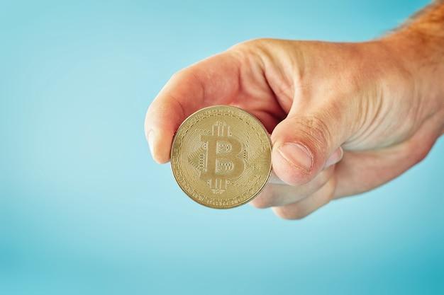 Человек, держащий в руке символ криптовалюты - электронные виртуальные деньги для веб-банкинга и международных сетевых платежей, выборочный фокус, тонированные