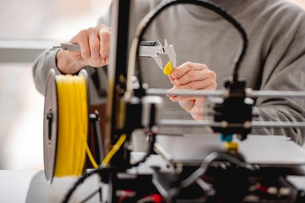 3d 프린터로 그의 손에 노란색 플라스틱 세부 인쇄를 잡고 측정하는 남자