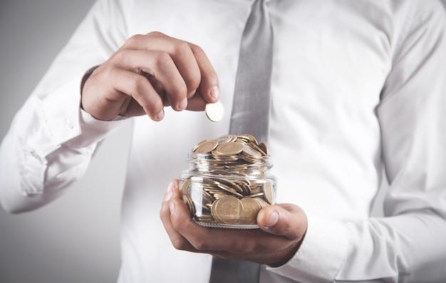 Мужчина держит банку с монетами.