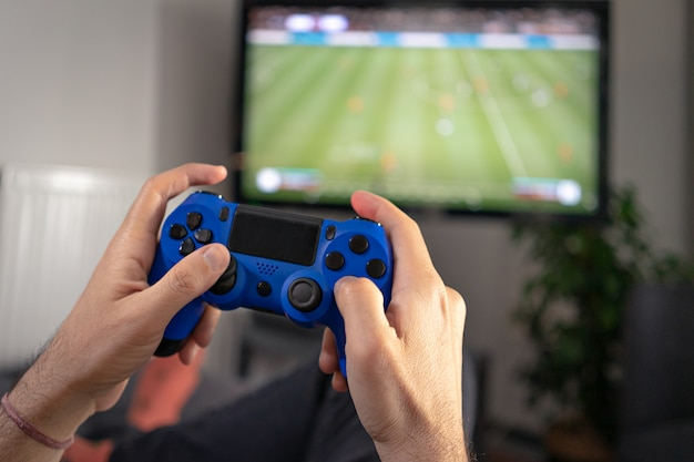 Man holding joystick and playing a video game at home