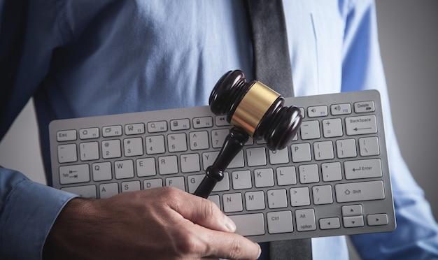 Мужчина держит молоток судьи с компьютерной клавиатурой. понятие интернет-преступности