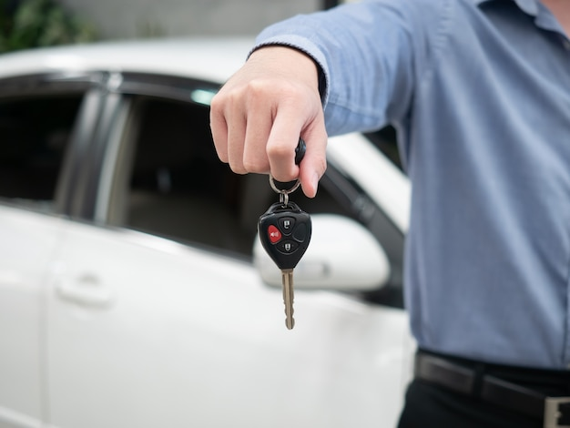 Man holding key in modern auto dealership. close up hand of cardealer giving car key to customer