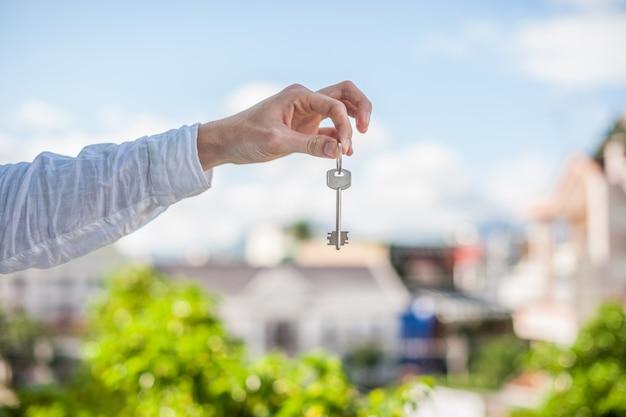 도시에있는 집의 배경에 집 열쇠를 들고 남자. 부동산 개념 다루기