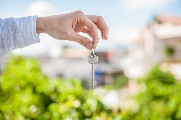 市内の家の背景に家の鍵を握る男。不動産の概念に対処する