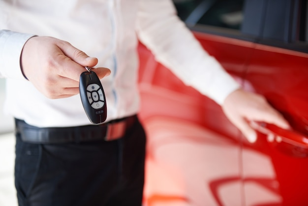 Мужчина держит ключи от нового автомобиля в автосалоне