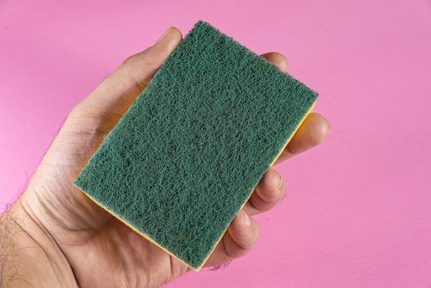 Man holding kitchen sponge on the pink background