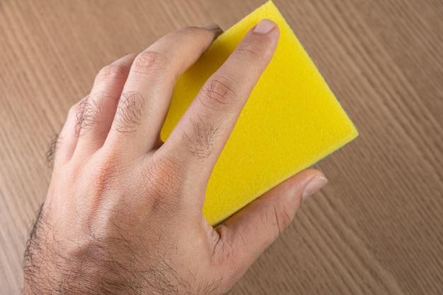Man holding kitchen sponge on the wooden background