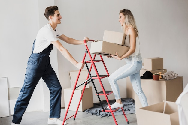 Мужчина держит лестницу для женщины, чтобы подняться