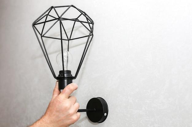 手にランプを持っている男。電気設備。モダンなロフトデザイン。屋内での修復。保守作業。