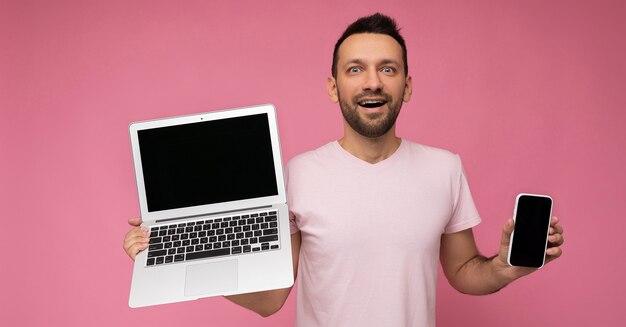 고립 된 분홍색 벽에 t- 셔츠에 노트북 컴퓨터와 휴대 전화를 들고 남자.