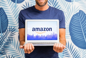 Man holding laptop with Amazon site