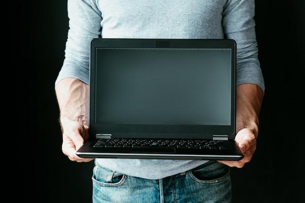手に空白の画面でノートパソコンを持っている男