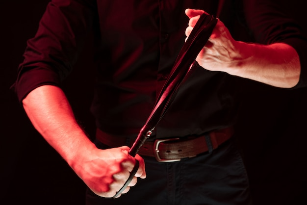 A man holding a leather whip. bdsm