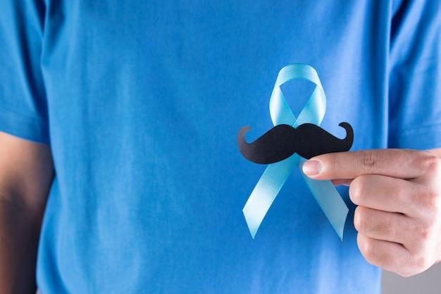 Мужчина держит голубую ленту с усами.