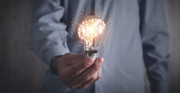 Человек, держащий лампочку и человеческий мозг. мозговой штурм. идея