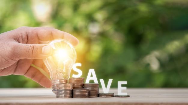 전구와 많은 성장 스택 동전을 들고 있는 남자 앞에 식물과 저장이라는 단어가 있습니다. 재정 회계를 위한 돈 절약 개념과 저축을 늘리기 위한 아이디어.