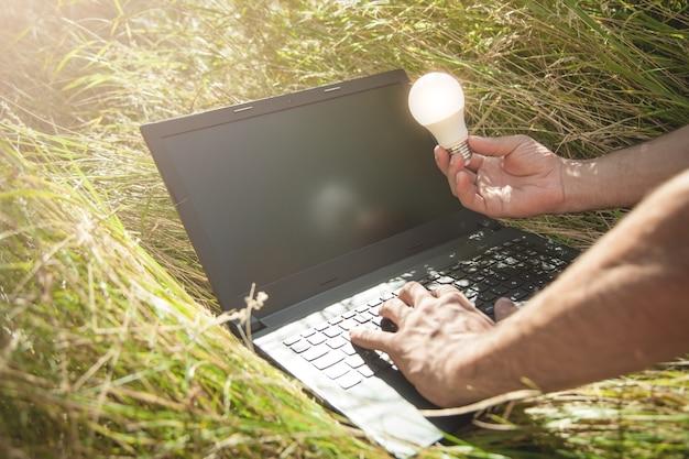 전구를 들고 자연에서 랩톱 컴퓨터를 사용하는 사람.