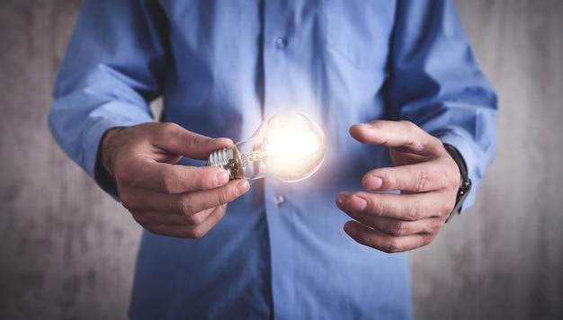 전구를 들고 남자입니다. 영감과 창의성의 개념