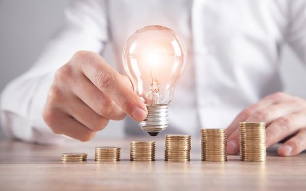 電球を持っている男。机の上のコインのスタック。エネルギーとお金の節約