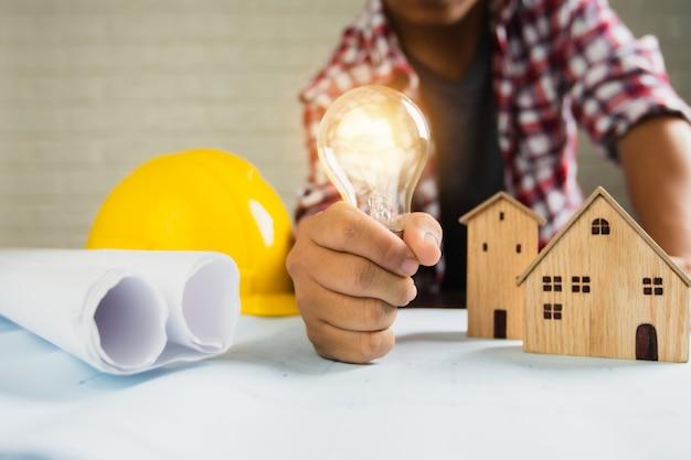 Man holding light bulb on toy house