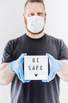 Человек, держащий лайтбокс с текстом, будьте в безопасности