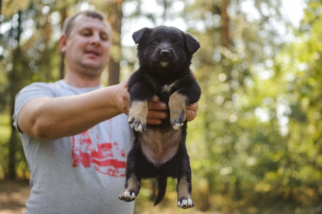 Man holding a little black puppy looking at the camera in the forest