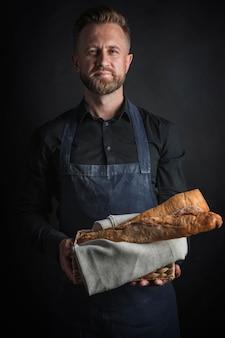 Мужчина держит буханки хлеба