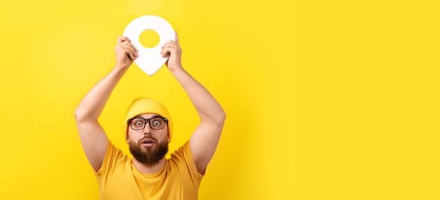 Man holding location marker over yellow background, concept navigation and exploration, panoramic image
